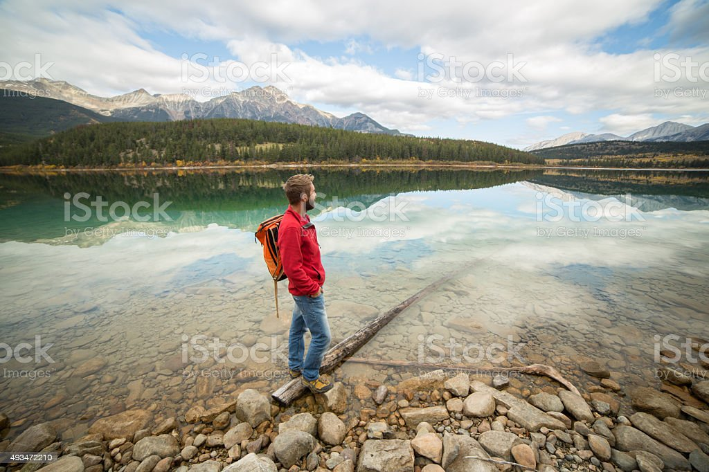 Young man standing on log contemplating the beauty in nature stock photo