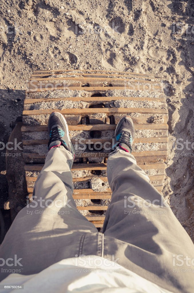 Young man standing on old machine tracks stock photo