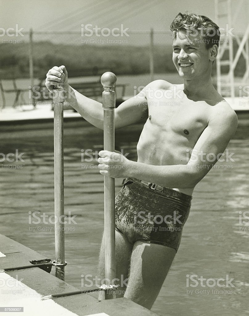 Young man standing on pool ladder, (B&W) stock photo