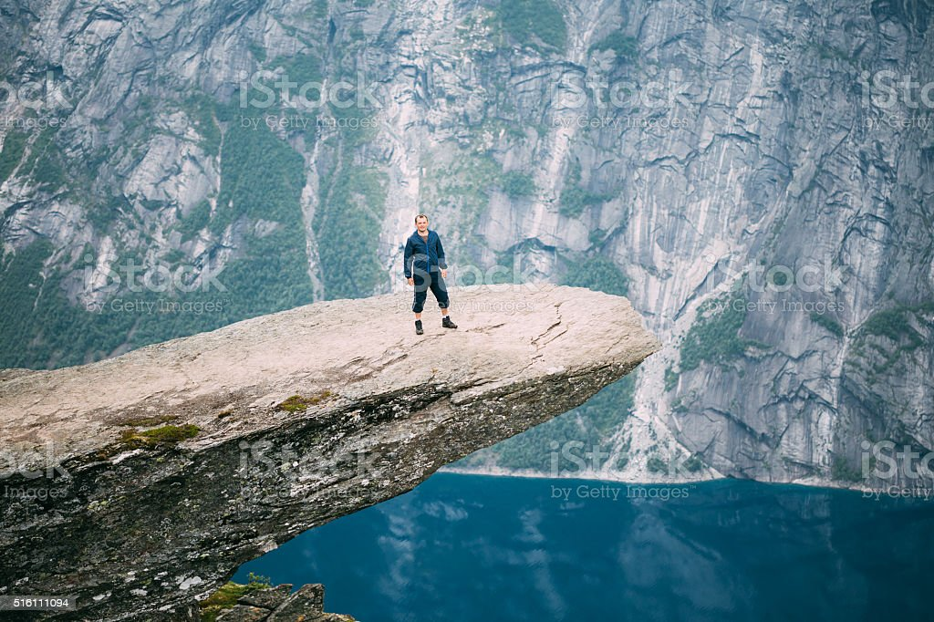 Young man standing on rock in the mountains of Norway stock photo