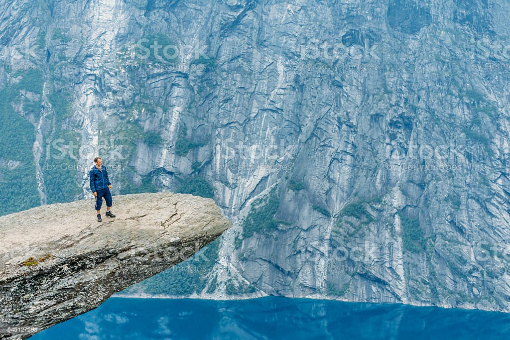 Young Man Standing On Rock In The Mountains Of Norway. stock photo