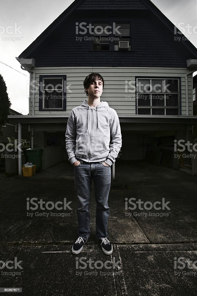 Young Man Standing Outside Gloomy House royalty-free stock photo