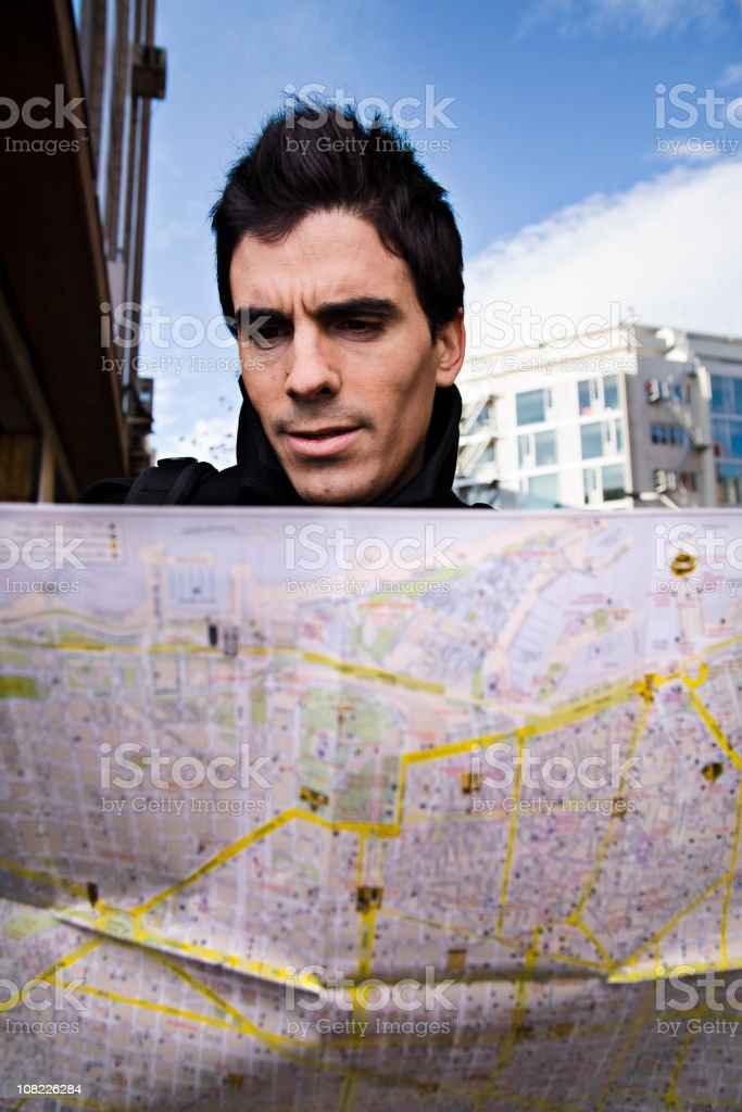 Young Man Standing Outside Looking at Map royalty-free stock photo