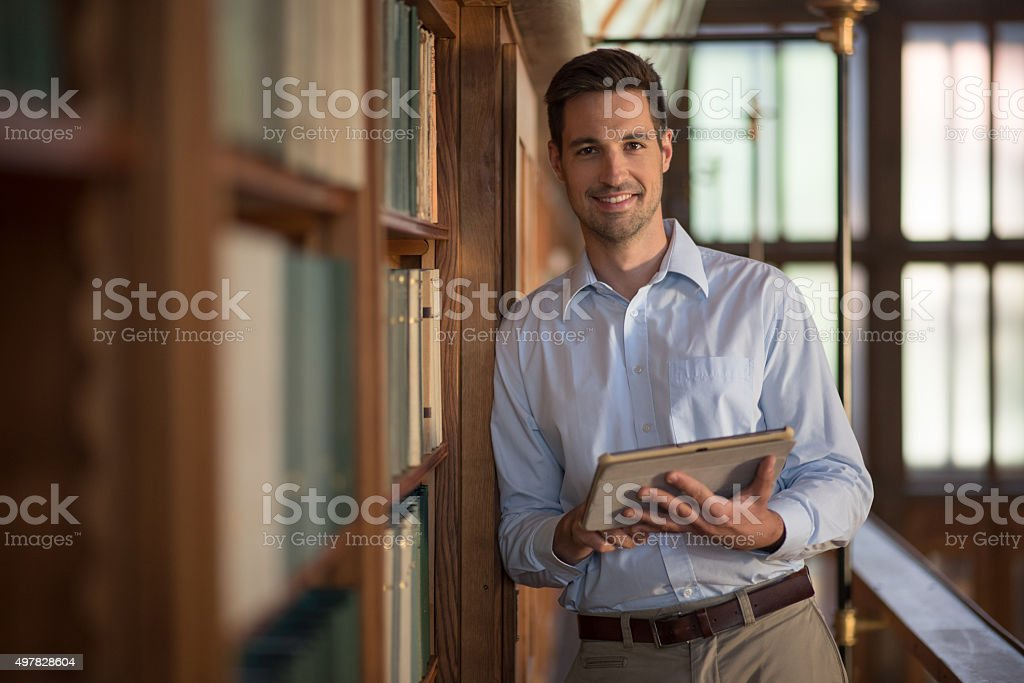 Young man standing with digital tablet in library stock photo