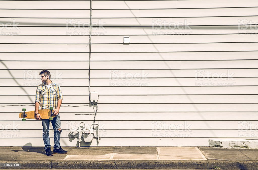 Young man standing with his skateboard royalty-free stock photo
