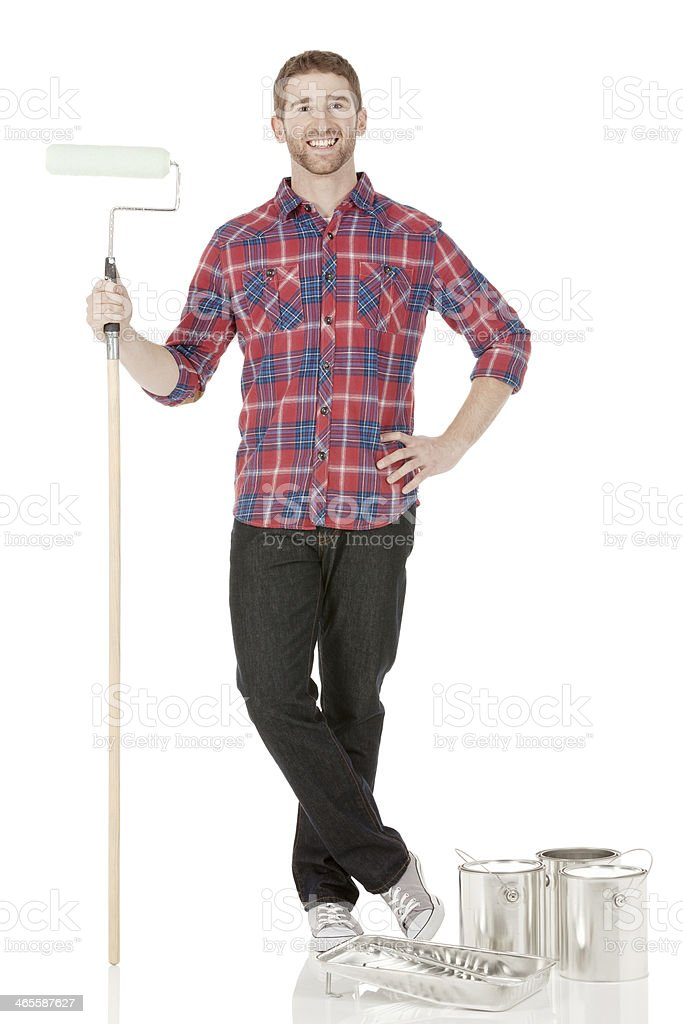 Young man standing with paint roller royalty-free stock photo