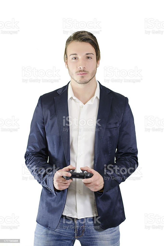 Young man standing, with videogame joypad in his hands royalty-free stock photo