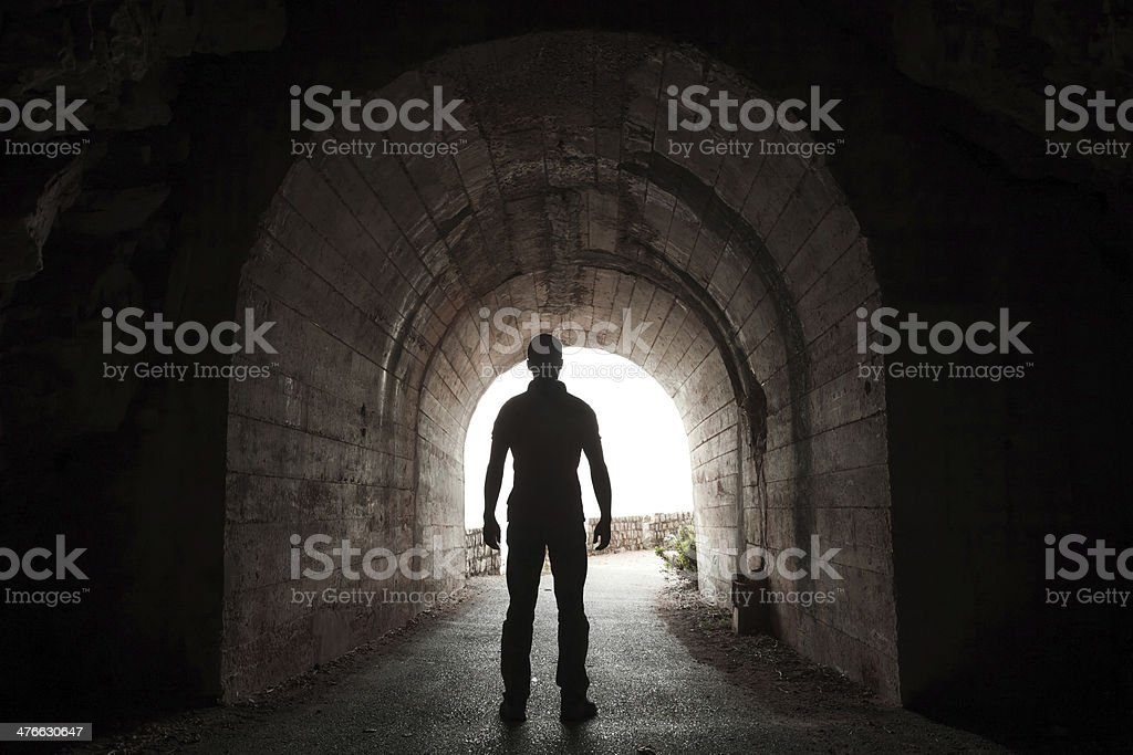 Young man stands in dark tunnel and looks out stock photo