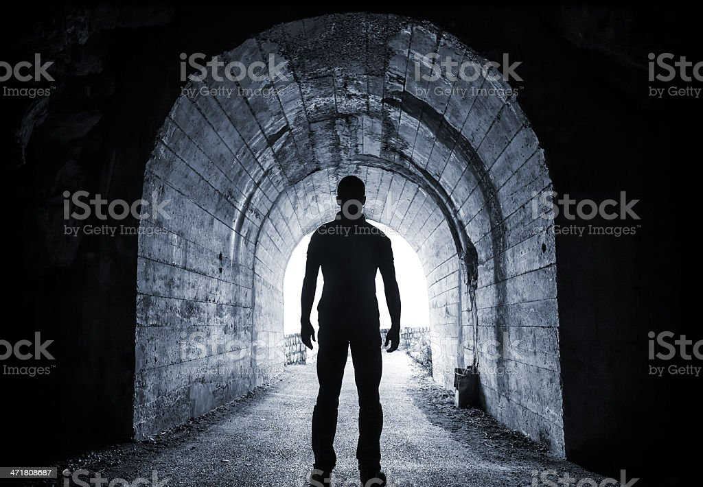 Young man stands in dark tunnel stock photo