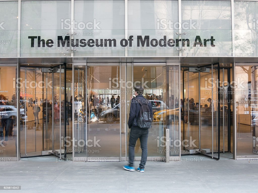 Young Man stands in front of MoMA stock photo