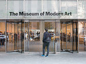Young Man stands in front of MoMA