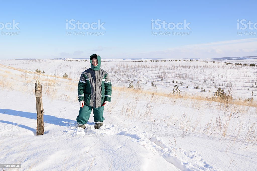 Young man stands on top of hill stock photo