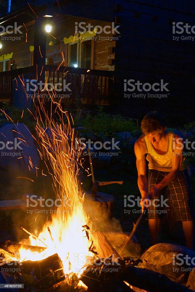 Young Man Stoking a Bonfire stock photo