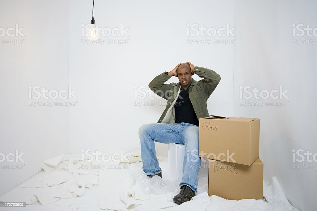 Young man stresses out about packing for a move royalty-free stock photo
