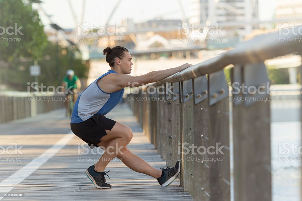 Young man stretching before jogging stock photo