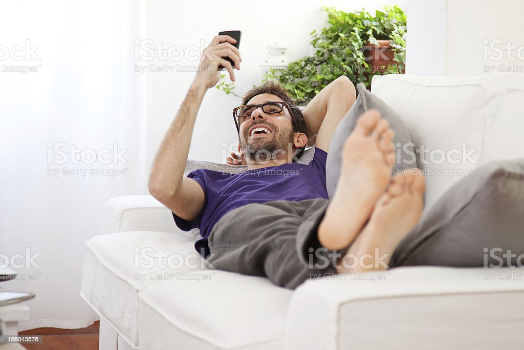 Young man stretching comfortably on couch royalty-free stock photo