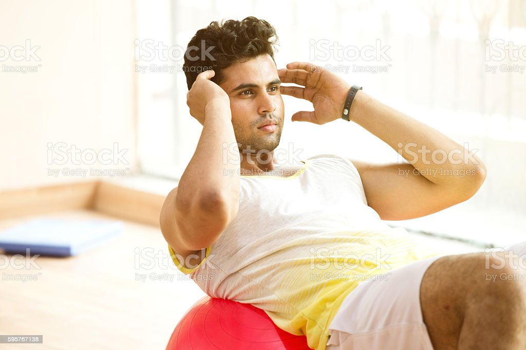 Young man stretching on exercise ball stock photo