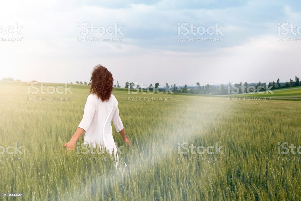 Young man striding through field of cereal plant stock photo