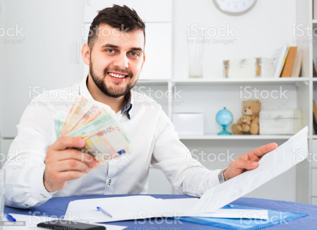 Young man struggling to pay utility bills and rent for his apartment stock photo