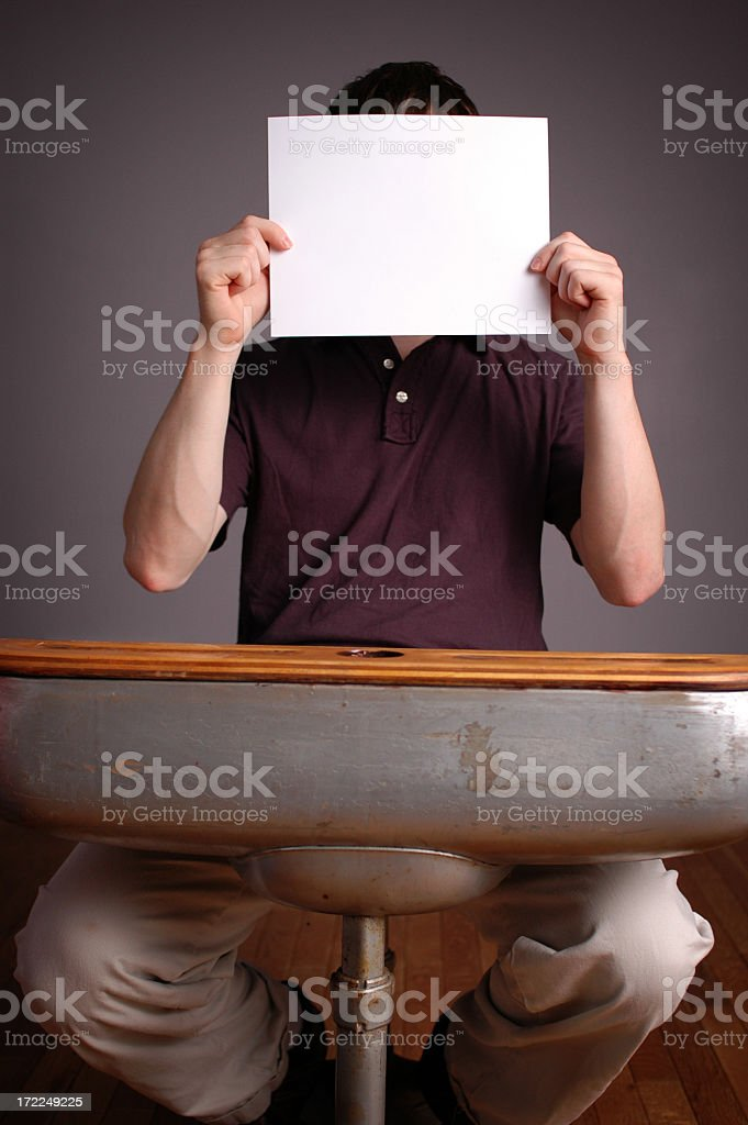 Young Man Student Sitting in School Desk Holding Blank Paper royalty-free stock photo