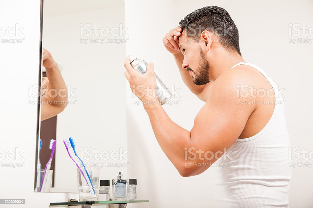 Young man styling his hair with spray stock photo