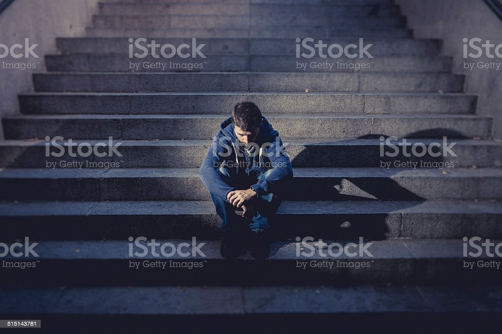 Young man suffering depression sitting on ground street concrete stairs stock photo