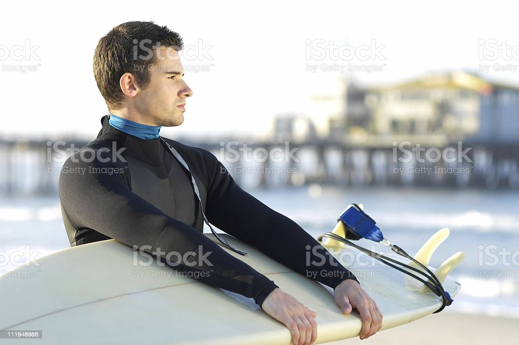 Young Man Surfer in Wetsuit with Surfboard and Pier Background royalty-free stock photo