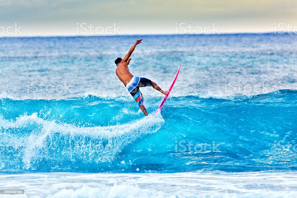 Young Man surfer Surfing in the Beach of Kauai, Hawaii stock photo