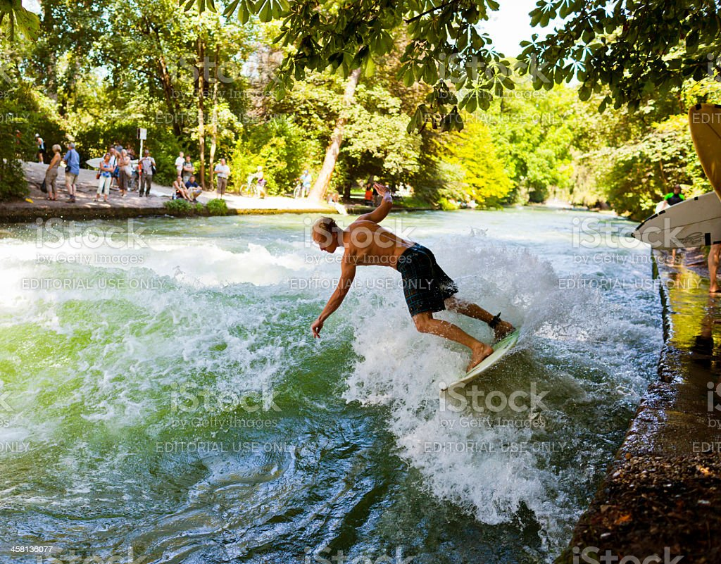 Young man surfing at the Eisbach river in Munich Germany royalty-free stock photo