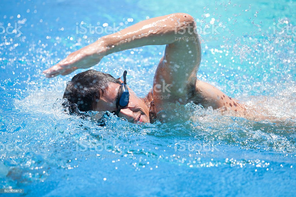 Young man swimming in a pool stock photo
