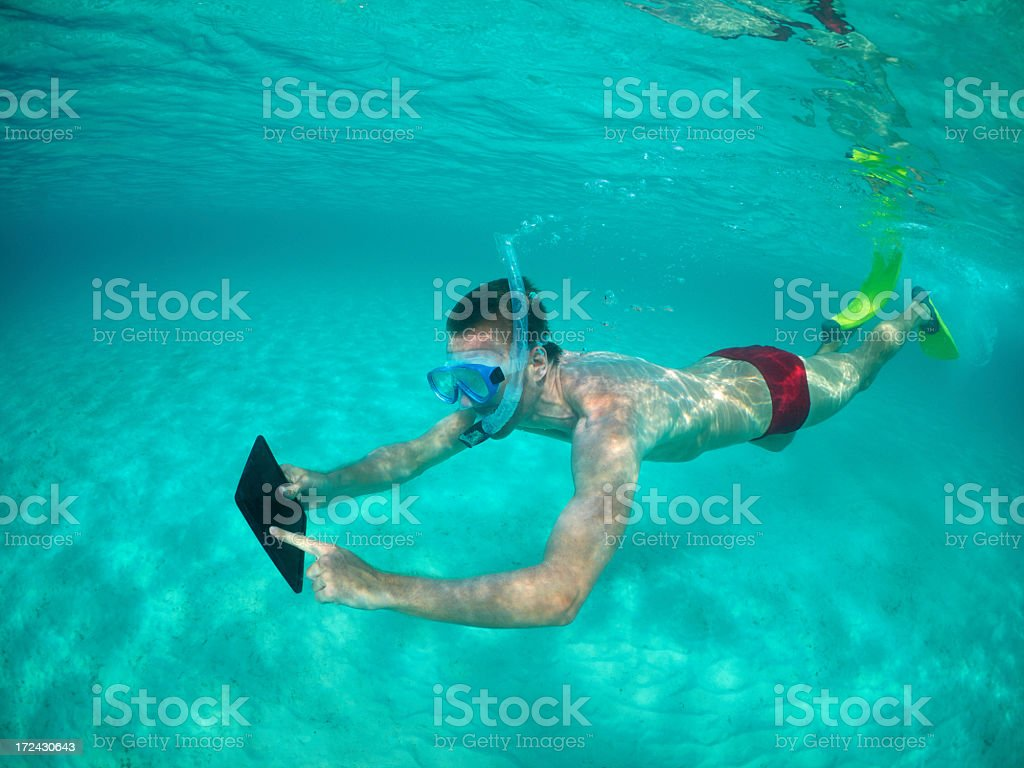 Young man swimming underwater with tablet royalty-free stock photo
