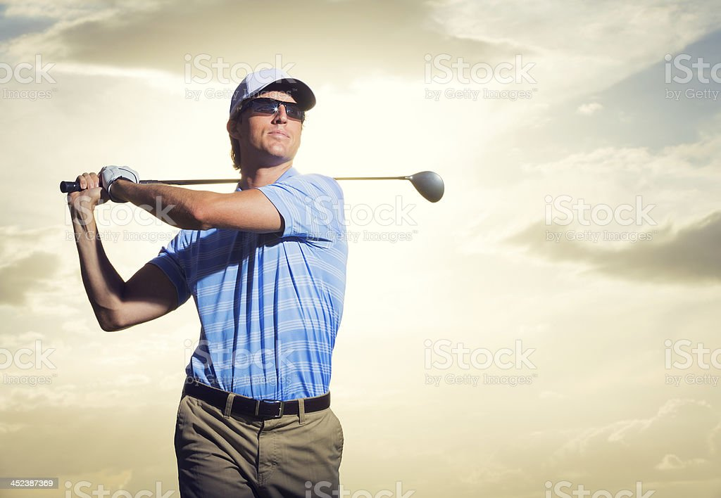 Young man swinging golf club stock photo