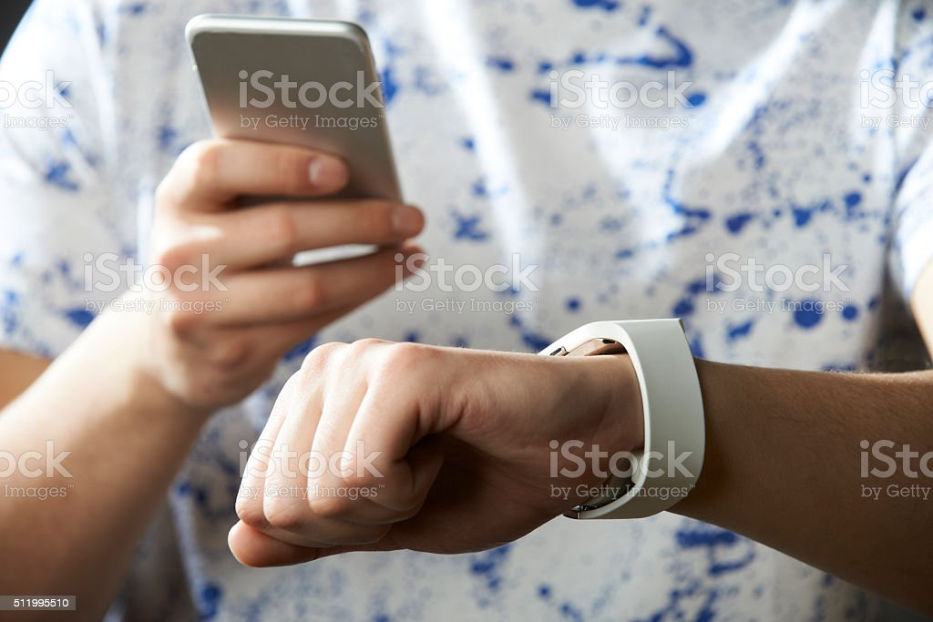 Young Man Synchronizing Smart Watch With Mobile Phone stock photo