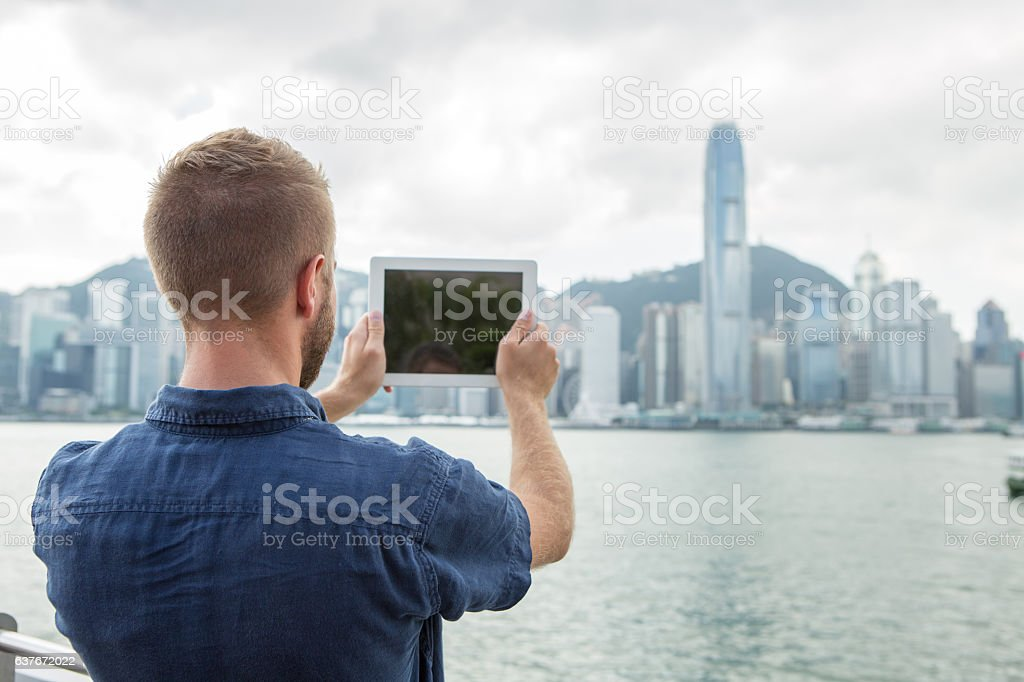 Young man takes digital tablet picture of Hong Kong skyline stock photo