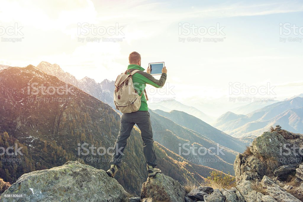 Young man takes digital tablet picture on mountain top stock photo