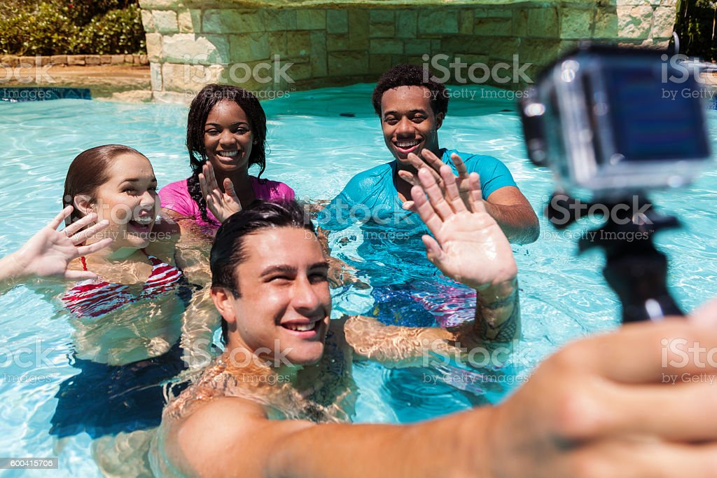 Young man takes photo with wearable camera in swimming pool stock photo