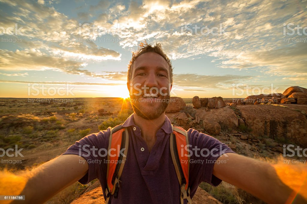 Young man takes selfie portrait with spectacular landscape at sunrise stock photo