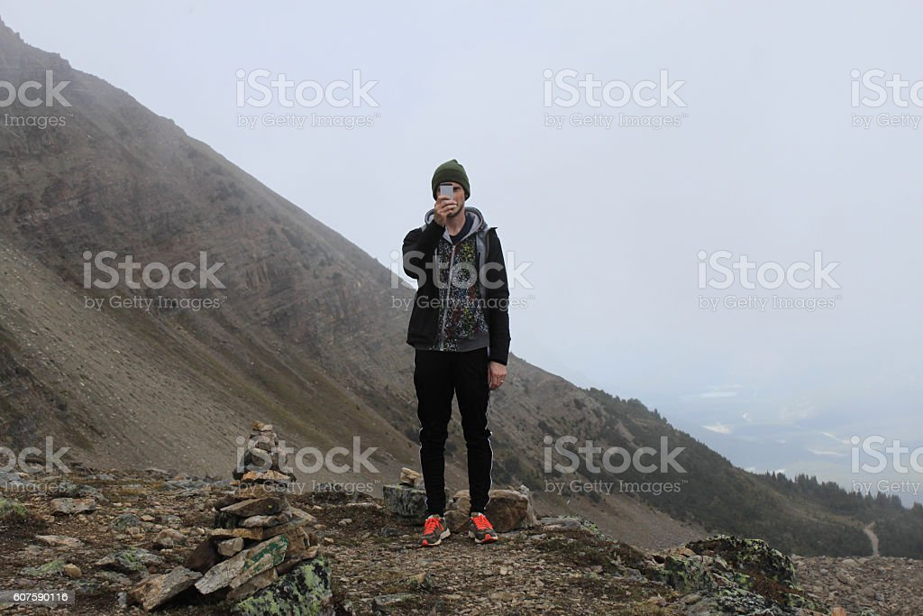 Young man taking a photo on a montaintop stock photo