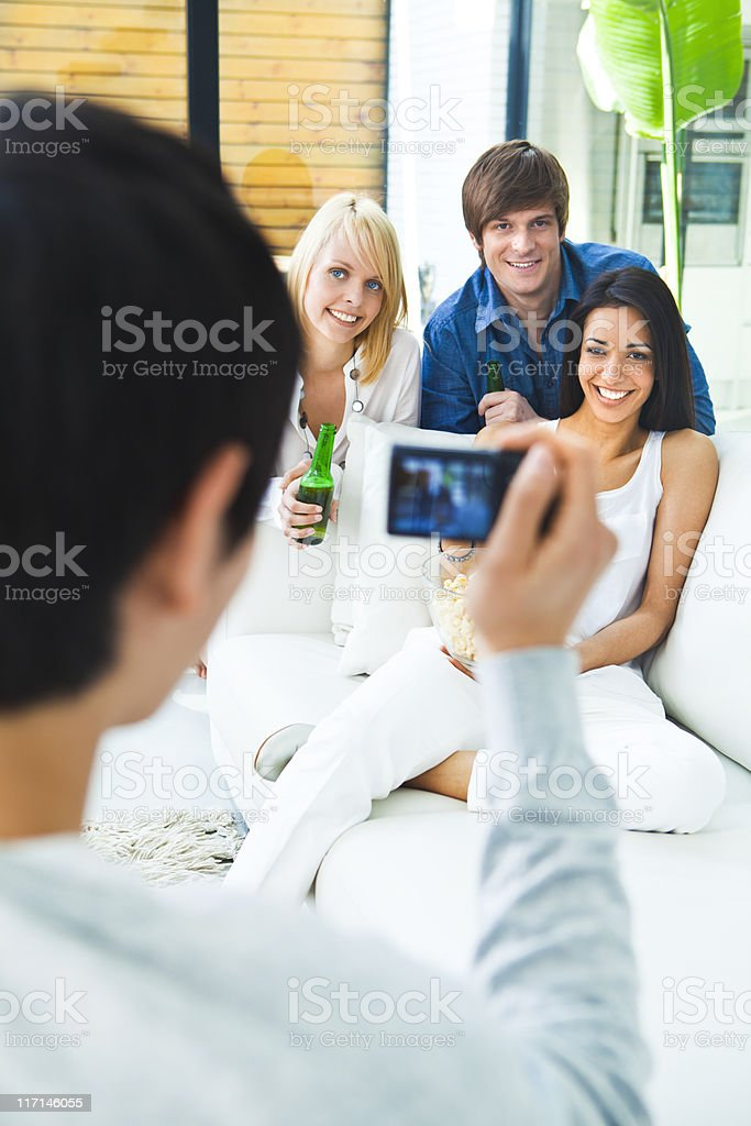 Young man taking a photo to his friends royalty-free stock photo
