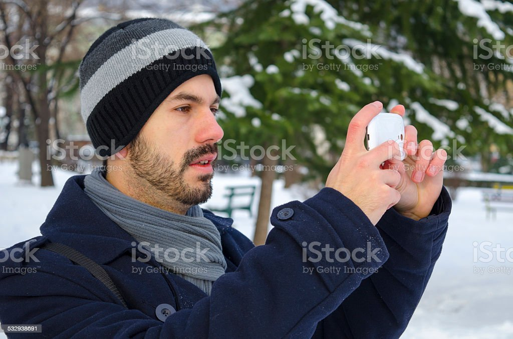 Young man taking a photo with his smartphone royalty-free stock photo