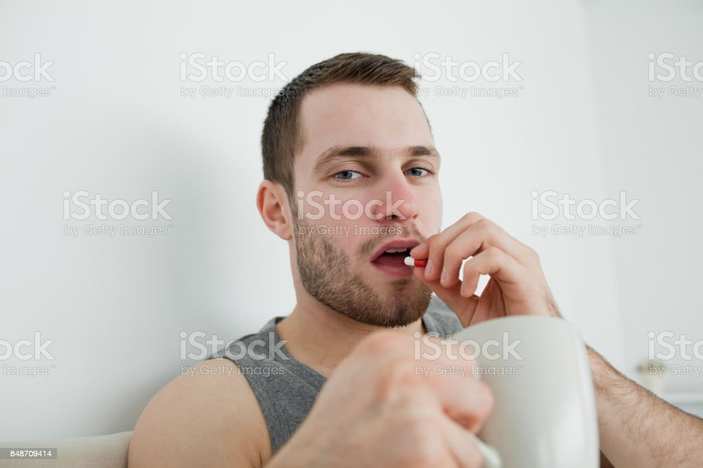 Young man taking a pill stock photo