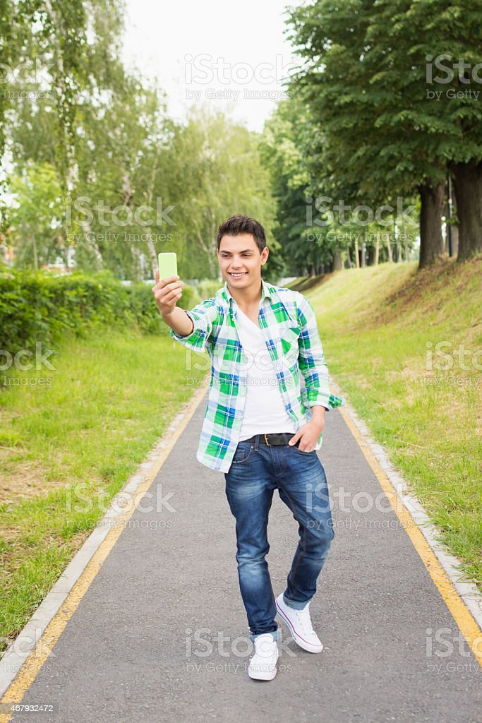 Young man taking a selfie in park in spring stock photo