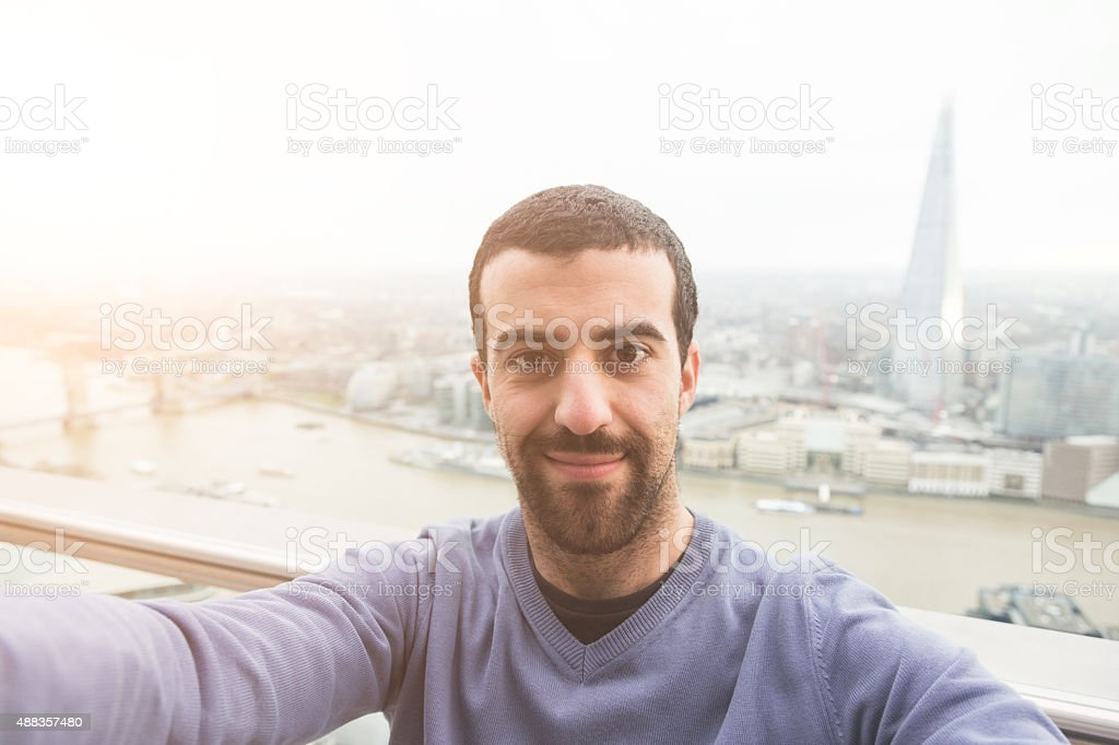 Young man taking a selfie with London cityscape on background stock photo