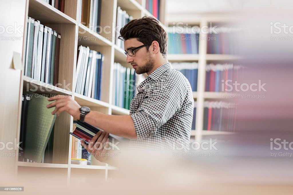 Young man taking books in a library. stock photo