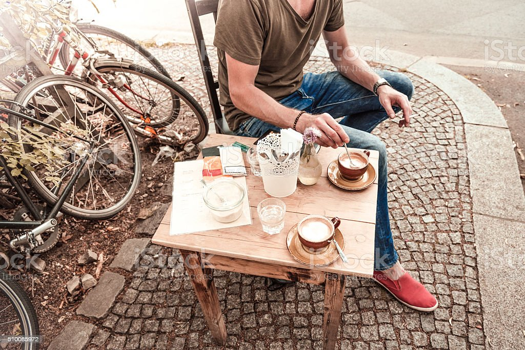 young man taking coffee in berlin street cafe stock photo