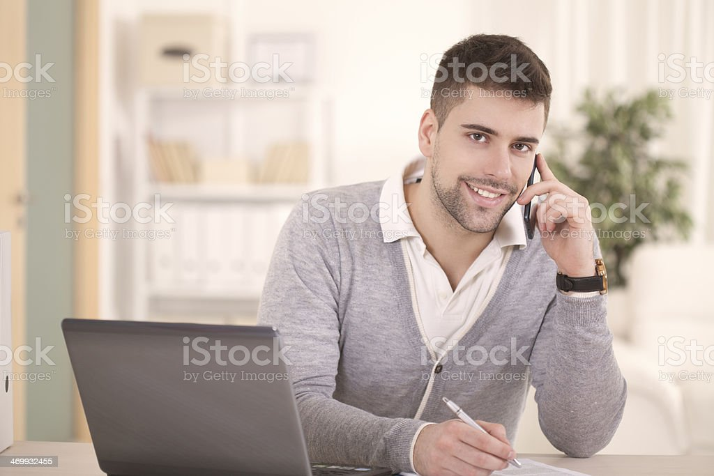 Young man taking messages on smartphone as he works at home royalty-free stock photo