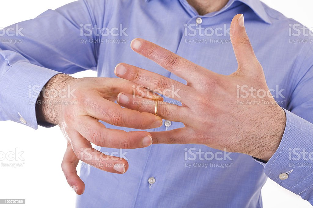 Young man taking off his golden wedding ring. royalty-free stock photo