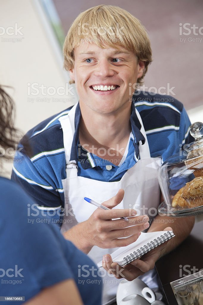 Young man taking order from customer at a coffee shop royalty-free stock photo
