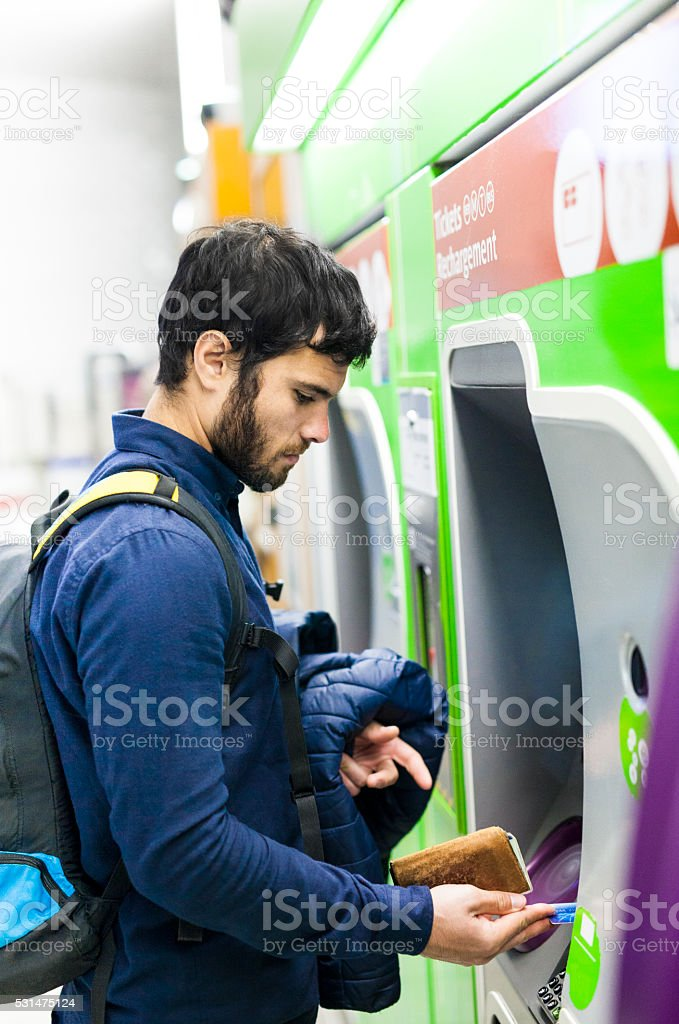 Young Man Taking Out Cash From ATM in Subway stock photo
