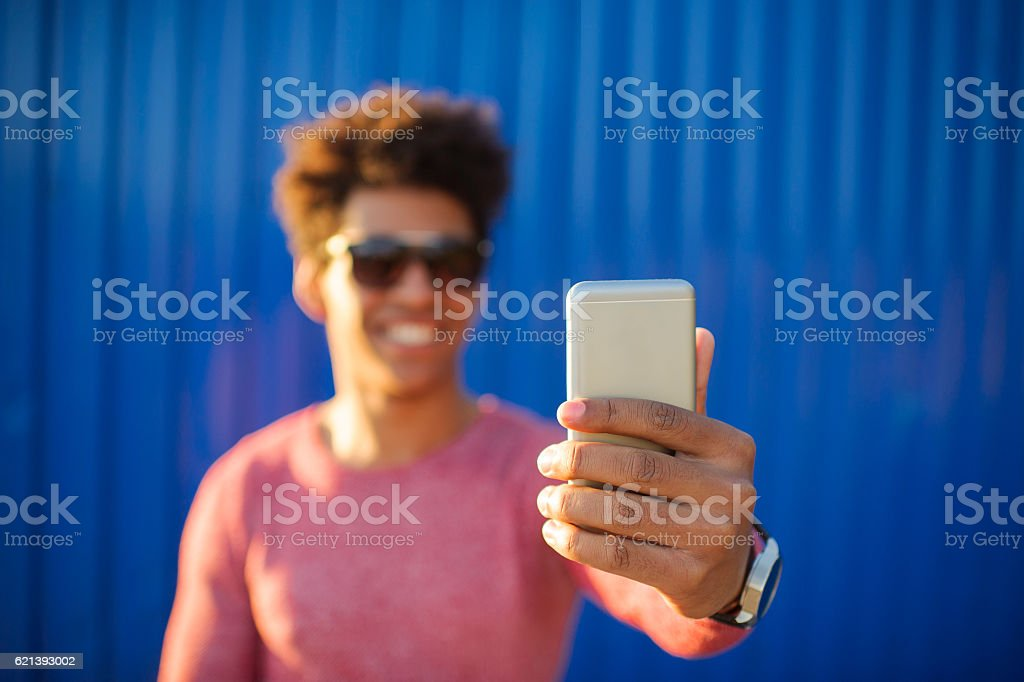 Young man taking self portrait with mobile phone stock photo